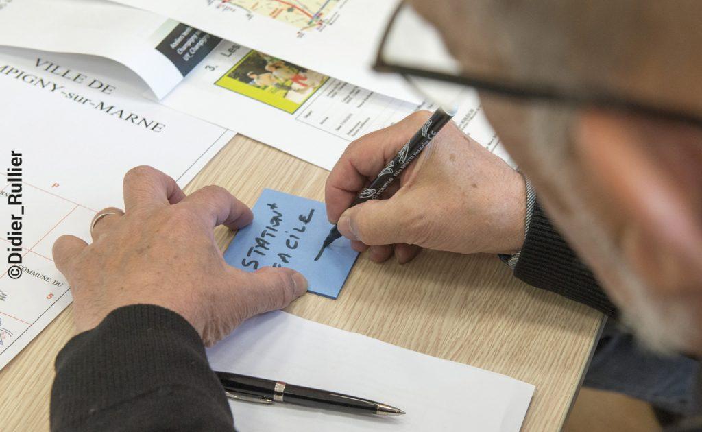 Personne écrivant sur un post it lors des ateliers de concertation avec les habitants de la Ville de Champigny