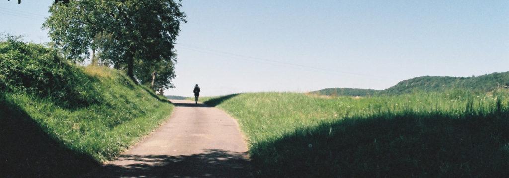 Une personne marche sur un chemin de campagne. Crédit photo : Elodie F.