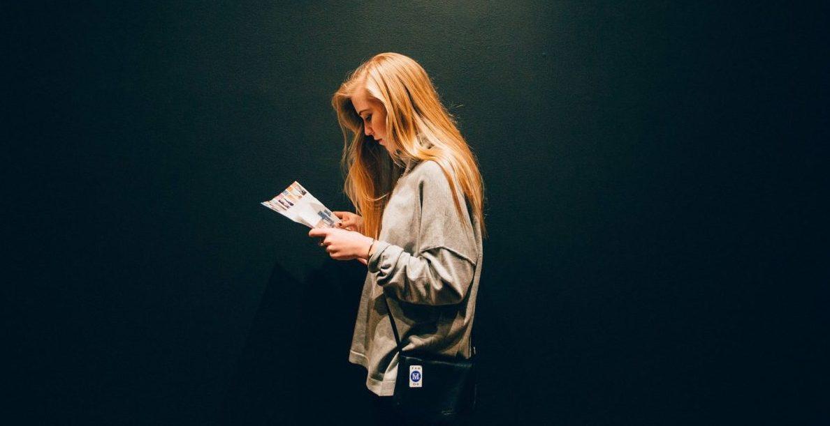 Une jeune femme lit un magazine.